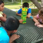 Five students look at a jenga game with yellow and green blocks