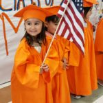a young girl in an orange cap and gown smiles and holds an American flag