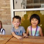 A group of pre-school aged children sit at a picnic table smiling