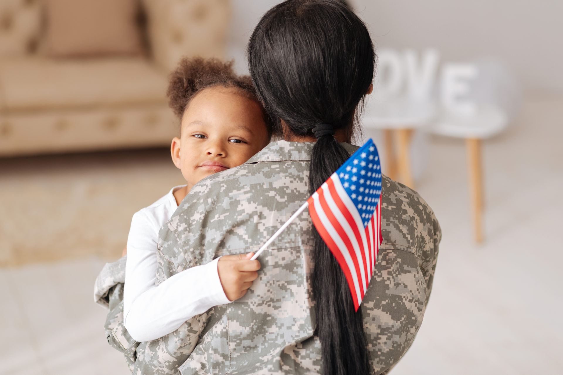 Child holding American flag hugs woman in military uniform