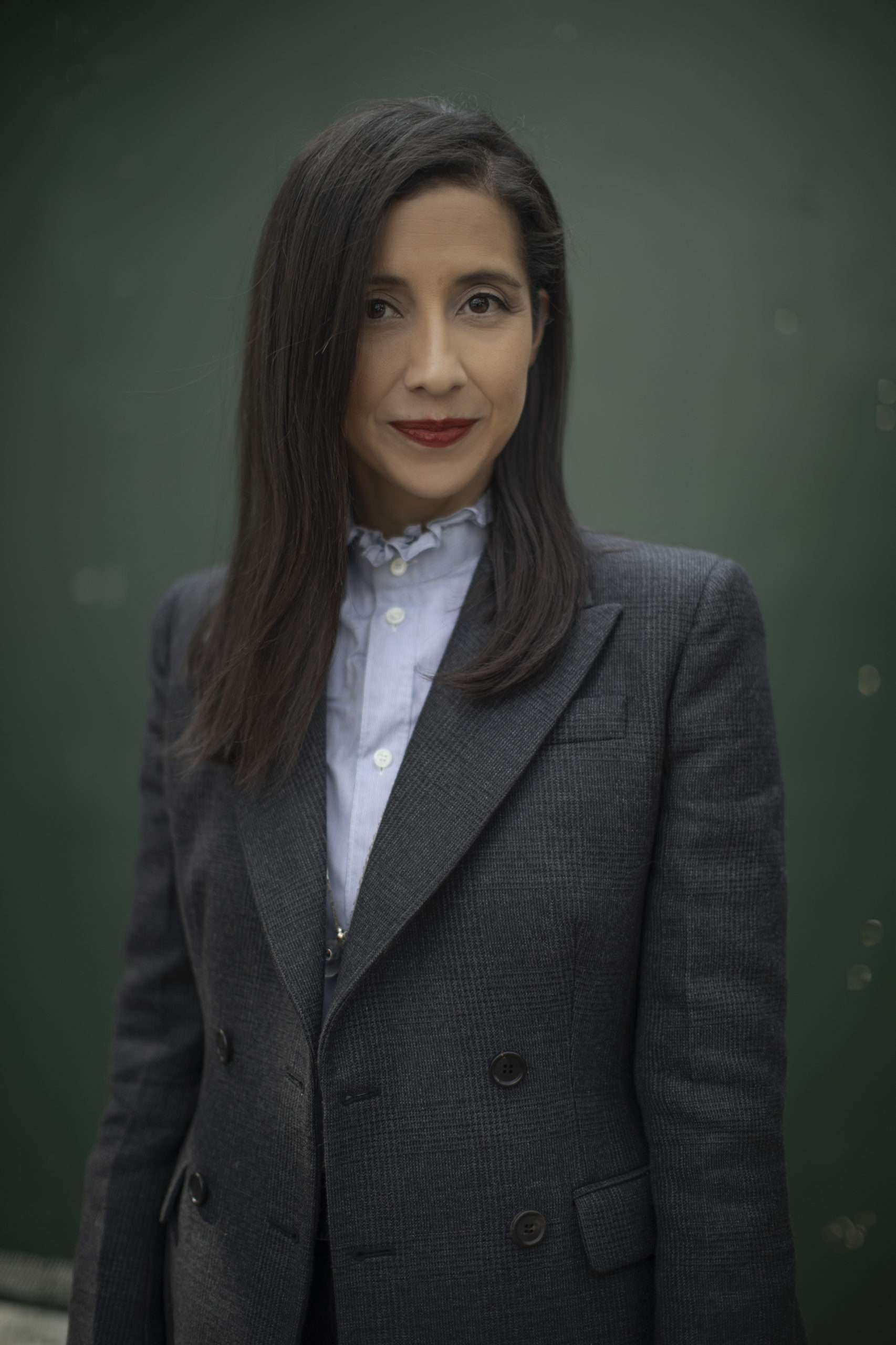A photo of Karla Martinez. She is wearing a dark gray blazer, blue high-collared button down shirt, red lipstick, and has straight brown hair. She is standing in front of a gray/green background