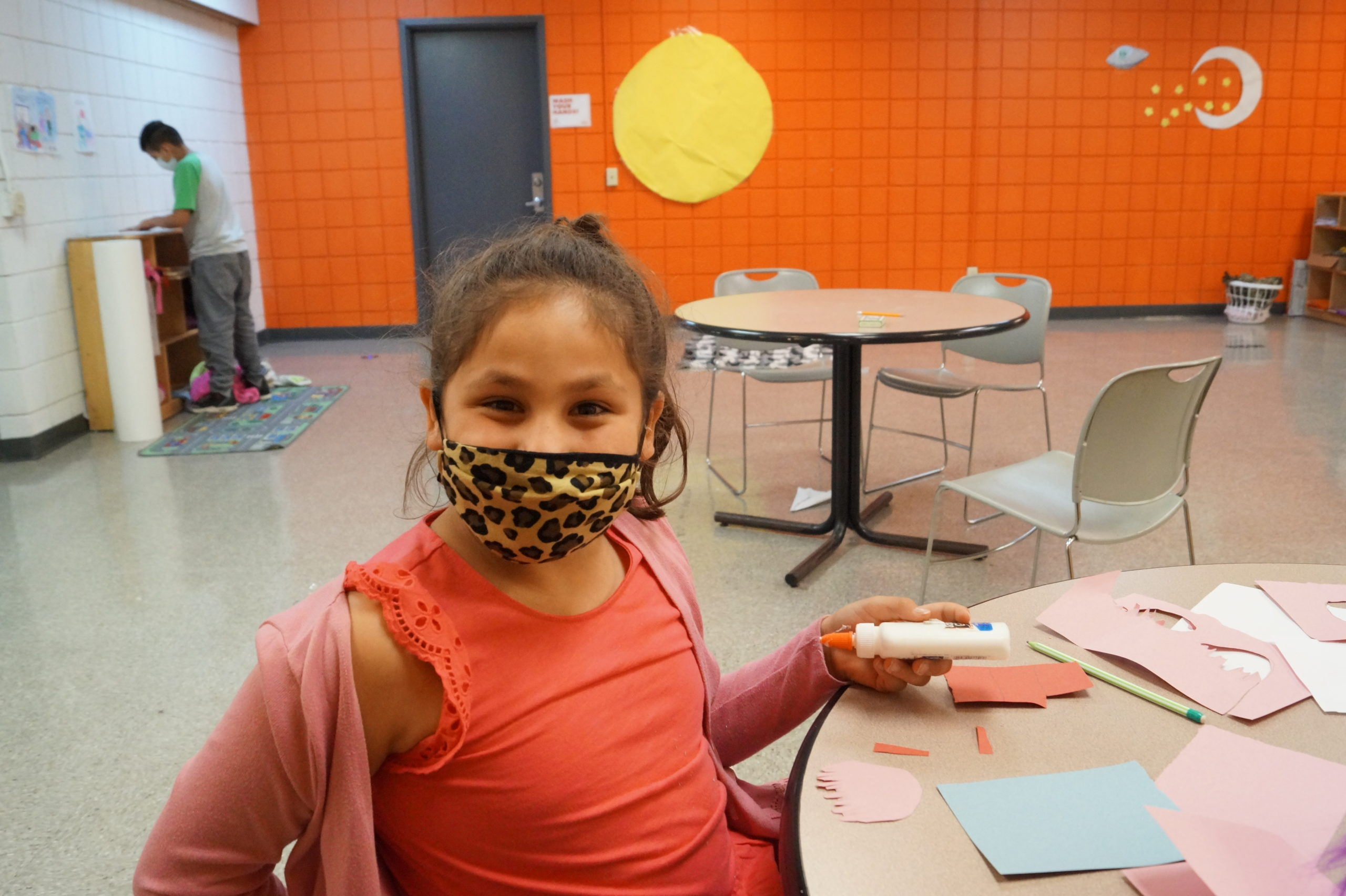 A young girl in an orange tanktop is wearing a leopard print mask over her nose and mouth and holding glue while sitting at a table