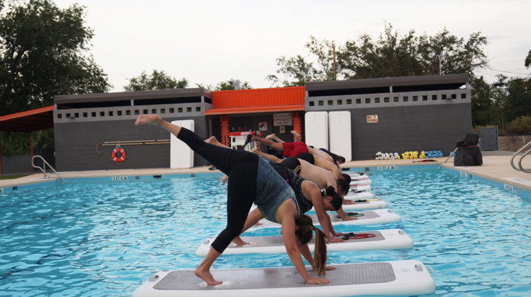 YWCA participants doing yoga on float fit boards