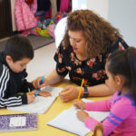 A teacher in a black shirt with flowers teaches a young boy in a sweatshirt and a young girl in a pink top at a YWCA Early Learning Academy