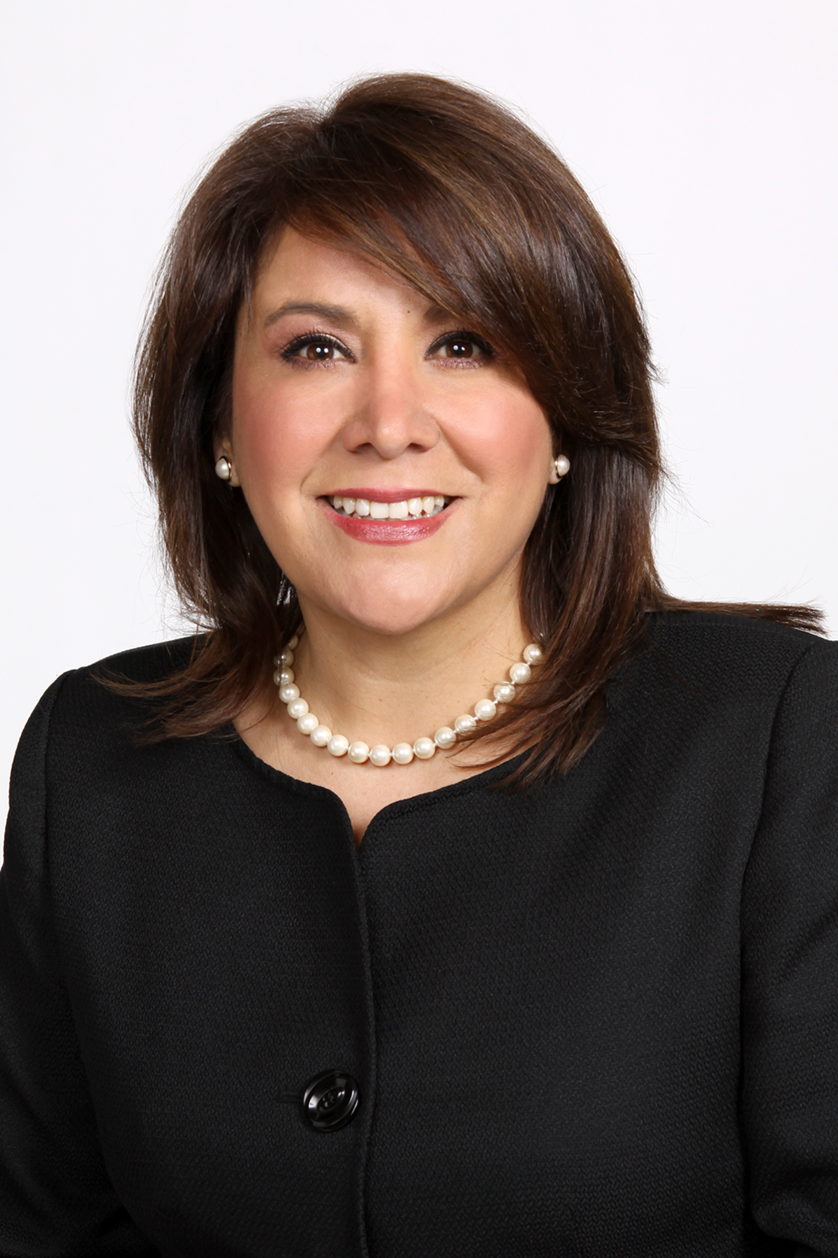 Photo of YWCA El Paso CEO in black top, pearl necklace, and pearl earrings