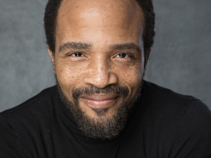 A photo of Broadway star James Harkness. A black man with a mustache, beard, and black hair. He is looking directly into the camera with a slight smile. He is wearing a black shirt and the image only shows him from the shoulders up.