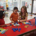 Three girls working on building a bridge