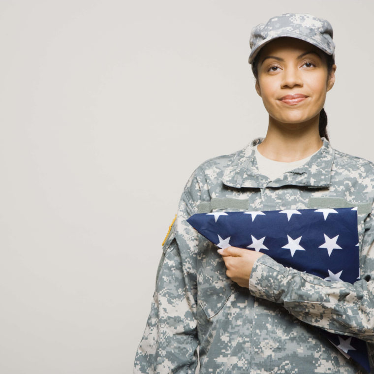 Woman in army uniform holding folded American flag