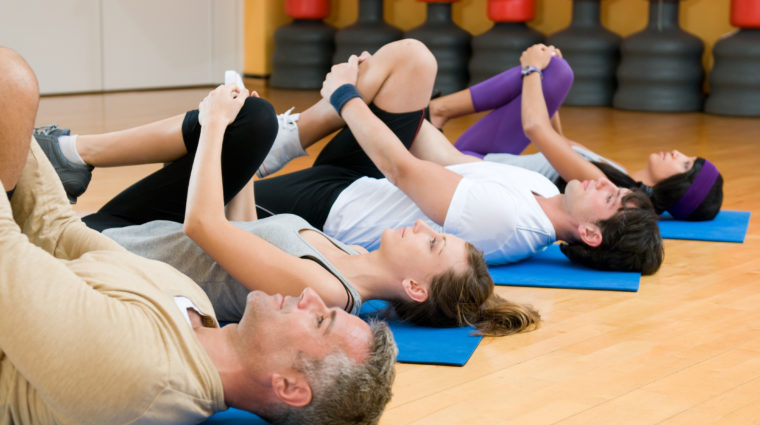 stock photo of four people stretching on mats in gym