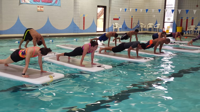 Photo of a dozen people in a pool on Float Fit boards