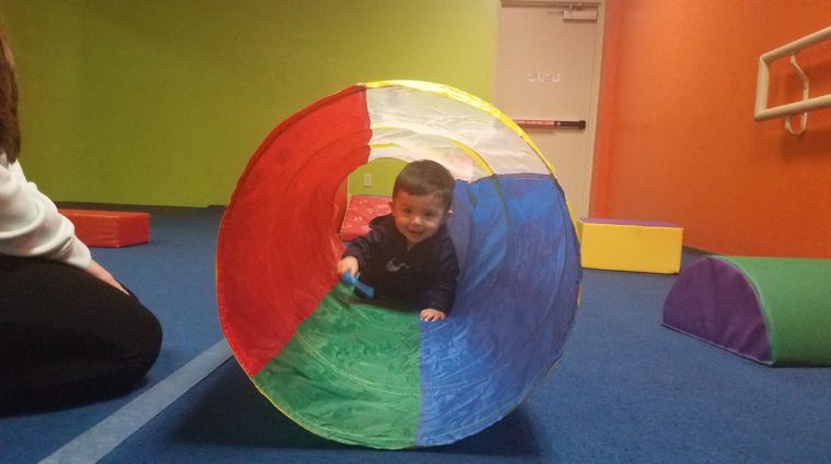 baby crawling through a multi-colored tube