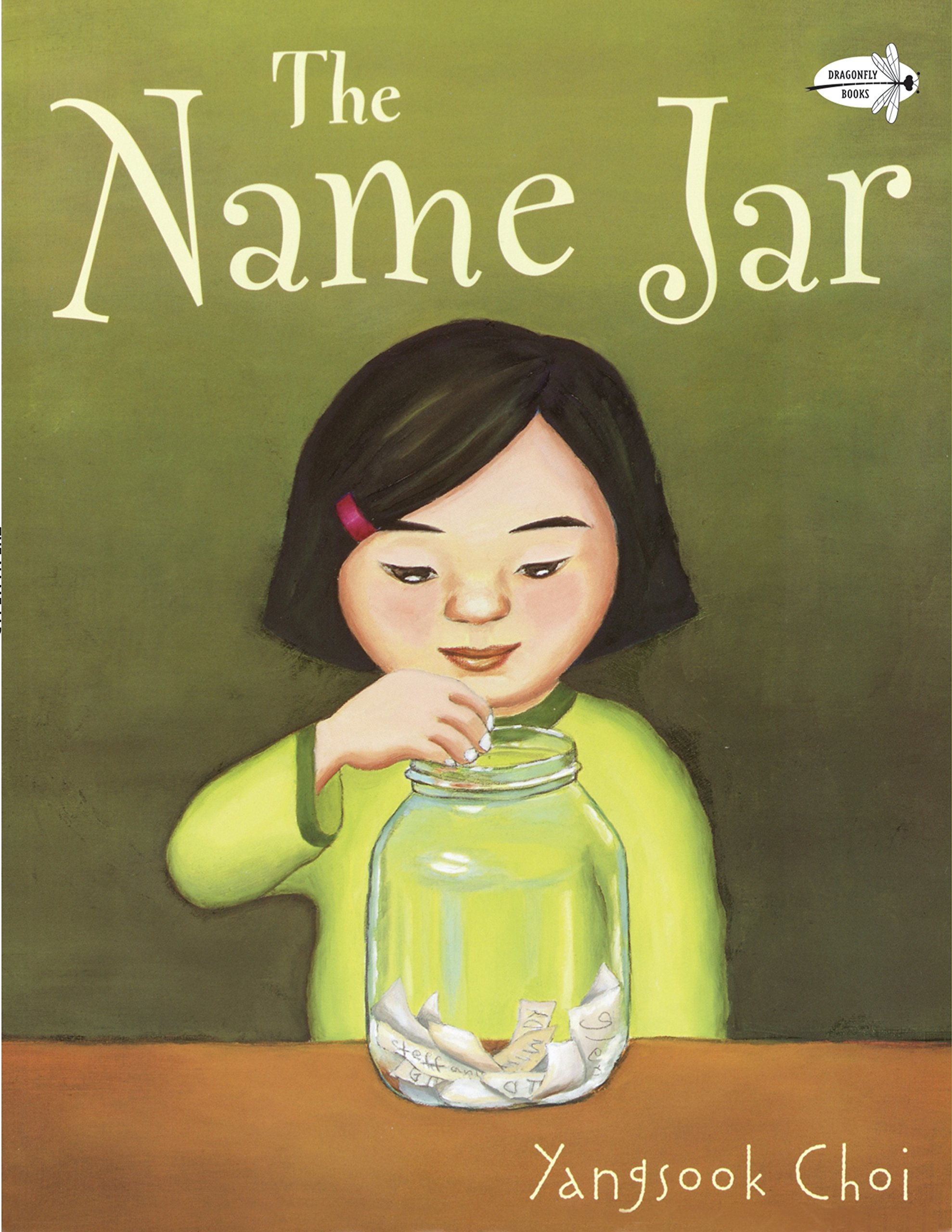 a young Korean girl with short black hair, wearing a green sweater has a jar with pieces of paper folded inside it. She is reaching in to pick a piece of paper. Above her is the book title: The Name Jar