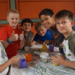 A group of six students smile over a science project at YWCA's summer camp